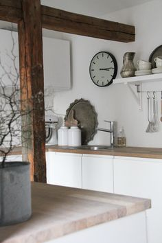 Ooooooooo! Love the rough cut beams against the stark white walls and then the smooth chopping block counters. Round clock and serving platter soften the sharp angles.