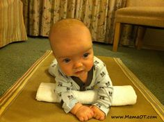 Roll up a receiving blanket and place it under baby's chest to assist with making tummy time easier and happier for baby! Lots more tips in the article to make tummy time easier and less miserable for baby.