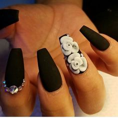 Matte black coffin shapped nails with white 3D flowers and swarovskis.