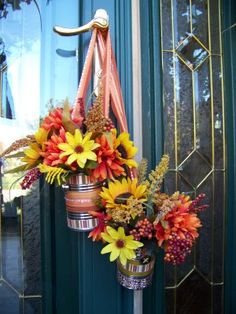 These are make with used fruit or veggie cans, drill one hole on each side of the can and tie a ribbon around them to make a hanger. drill a couple holes in the bottom for drainage and add your favorite fresh fall flowers!