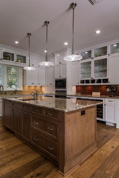 Three contemporary-style pendant lights illuminate this kitchen's contrasting island that serves to moderate the white perimeter cabinetry while coordinating with the backsplashes on the outer walls. Neutral granite countertops give the room a cohesive look.