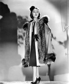 Fay Wray in a stunning outfit with a typical late 30's / 40's silhouette. Wearing a beautiful hat and a cape trimmed with fur.