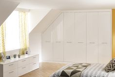 Minimalistic white fitted wardrobes, combined with light wood, yellows and grey for that Scandi look.