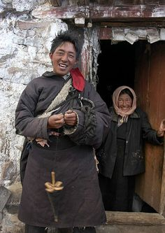 Young Couple on the Tibetan Plateau A young man spins wool like his ancestors did while his wife looks on from the doorway.  Tsurphu Valley, Tibet.