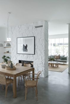 Polished concrete floors are paired with a timber dining table set and a limewashed free-form stone fireplace in this dining room. Houses Architecture, Timber Dining Table, Fireplace In Dining Room, Gas Fireplace, Dining Area, Dining Rooms, Contemporary Beach House, Polished Concrete, Open Plan Living