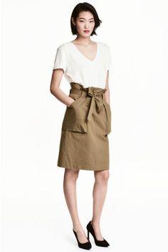 Gonna cargo in tessuto di misto cotone. Tasche applicate davanti, alta cintura da annodare in vita. Abbottonatura con cerniera e gancetto.