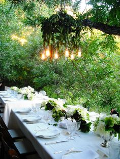 Custom vintage inspired outdoor chandelier hangs over a two long tables at an outdoor wedding