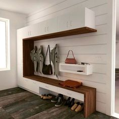 A modern take on the traditional mudroom lockers design featuring a walnut bench that wraps up a tall storage cabinet and frames in the hanging space. Painted white shiplap walls give a perfect backdrop to the white cabinets. A small shelf floats on one side to drop your keys as you come in the door from the garage. BONUS: This was designed with budget in mind and can be completely built with IKEA cabinetry with their walnut countertops. Designed by Labra Design Build.