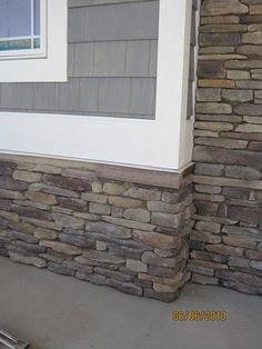 dark gray siding, white trim, stone