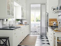 A small country kitchen with white drawers, doors and black countertops.