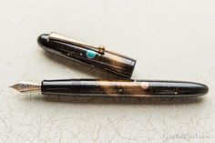 This Namiki maki-e fountain pen was released in November 2016 by maki-e artisan Michifumi in Japan. It features the Togidashi Maki-e technique (burnished maki-e) and Raden techniques, depicting a sparkling cosmic galaxy scene. The pen has a fine 18kt gold nib, fills via cartridge/converter (a CON-70 is included), and comes packaged in a wooden box with a bottle of ink.<br><br><i>Please allow us up to several extra days for shipping of this pen. Please also note we are ...