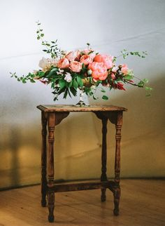 Low centerpiece style with gold pedestal bowl and pink peonies instead of coral