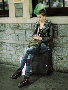 Female punk with a green mohawk, sitting on luggage,  smoking and on a cell phone