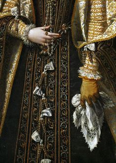 Tudor accessories: This woman holds a handkerchief in her gloved hand. The lacy band may be pulled-thread work, an early form of lace-style decoration, which is essentially making strategic holes in the cloth. Note the gold aglets down the front of her gown. They were common ornaments on clothing of the day. Henry VIII was fond of tearing his from his clothes and giving them as gifts.