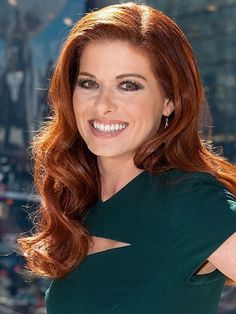 Debra Messing's side-parted curls hairstyle with a brown smoky eye and glossy lips | allure.com