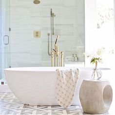 Luxurious master bathroom boasts an oval freestanding bathtub paired with a polished brass floor mount tub filler and positioned next to a concrete accent table in front of a seamless glass shower on white and gray geometric floor tiles.