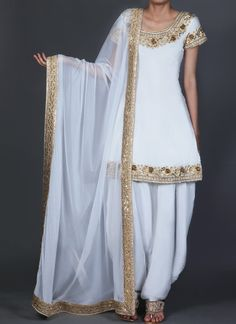Lashkaraa White and Gold Embroidered Punjabi Suit features a silk kameez alongside a santoon bottom and inner. An embroidered net dupatta completed the look. Embroidery work is done with zari and handwork stone embellishments. Pakistani Formal Dresses, Pakistani Dress Design, Pakistani Outfits, Indian Dresses, Indian Outfits, Stylish Dresses For Girls, Stylish Dress Designs, Kurta Designs, Simple Indian Suits