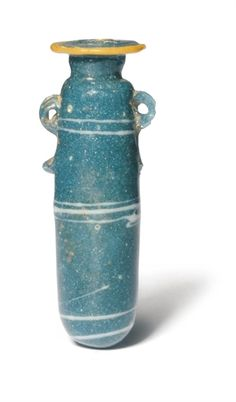 AN EASTERN MEDITERRANEAN CORE-FORMED GLASS ALABASTRON  CIRCA 5TH CENTURY B.C.  The dark turquoise body wound with three groups of fine marvered white spiralling threads, an applied yellow trail around the everted rim edge, applied twin 'duck head' handles  3½ in. (9 cm.) high