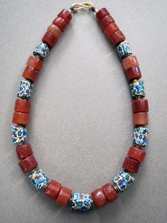 by Luda Hunter   Old Millefiori star murrine Venetian glass beads traded in Africa are combined with old carnelian stone beads. Gold vermeil bead caps surround the Venetian beads with African Vulcanite heishi spacers throughout the necklace as protection between each bead. Finished with gold vermeil end beads and clasp.   262$