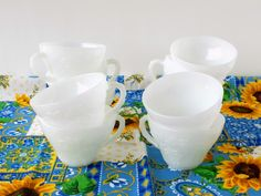 """The exquisite presence of white......a visual feast...... A lovely set of TEN (10) white milk glass cups.....nice as wedding and tea party tableware and glassware. Beautiful items for white home decor. Let a young girl enjoy them as her own tea party cups. Pretty tea cups with a feminine and flirty scalloped handle. From research, I believe these were manufactured by Anchor Hocking. each cup hold 3/4"""" cup to the very top each one is a little over 2 1/4"""" high and 3 1/2"""" across the top grape…"""
