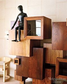 Kelly Wearstler's Ultra-glam Beach House - In the living room, a jointed figure traditionally used by art students sits atop a wooden cabinet, a jazzy neo-constructivist improvisation on the square designed by Pennsylvania furniture artist Jeffrey Greene. The vintage curved white chair is a Karl Springer design.