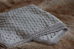 This Knot Stitch Baby Blanket is knitted flat and constructed using a repeating textured 'knot' pattern, complete with a non-rolling edged border.