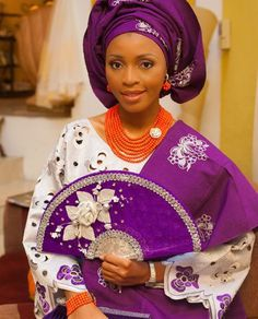 Nigerian bride in white and purple asooke. Flawless makeup by Sit pretty beautifiers. Photography by photos by Demi Red instead of the white on the fan