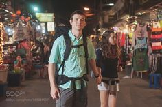 Caucasian tourists holding hands in market at night by gabledenims