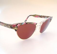 This is really a cool and about unique around piece! Made in France during the 80s, in a beautiful 50s style. Theyve a Lovely floral printed/ transparent material and a mix of the classic club master and cateye shades.... Sunglasses new and unworn from deadstock  Frame width 5,7 in 14,4 cm lens width (cal) 2 in 5 cm arms length 5,2 in 13,3cm -   Handling time & shipping policy  - Your Items will come in a free pouch bag (original one if available, see description) and get packed in a...