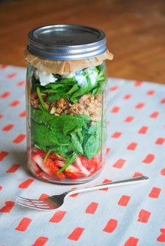 Strawberry and goat cheese mason jar salad with a brilliant trick to store dressing: place a piece of parchment paper on top of the jar and put the dressing on top of it.