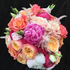 Coral and pink wedding bouquet including Miss Piggy Roses, vuvuzela roses, David Austen Juliette roses, sweet Avalanche roses, Barbados spray rose, Kloon rununuculus, astilbe and peonies Bijouxfloral.co.uk