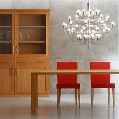 The FLOS 2097 pendant light shines in this minimalist interior with a wood display cabinet and bright red chairs.