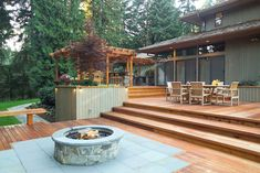 A 1700 square foot, 2-level deck, outdoor kitchen, and firepit complete the outside of this ranch-style home tucked among towering fir trees in a Seattle suburb. Description from homeandgardenphotos.photoshelter.com. I searched for this on bing.com/images