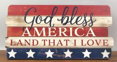 "Wooden sign in red, white, and blue ""God Bless America Land That I Love"" has a center bracket on the back to hang or can be set on a table or bookcase. Measures"