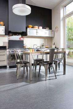 Gray cork floors in a free-standing stainless/wood/white kitchen