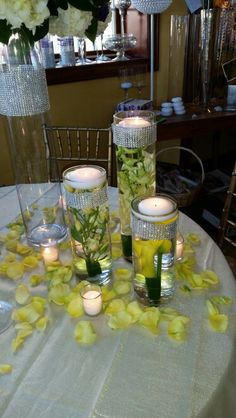 Trio of cylinders filled with yellow calla lilies, yellow spray roses and yellow dendrobium orchids, topped with floating candles and surrounded by rose petals.  DorisTheFloristt.com