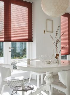 Our crisp, clean, tailored Luxaflex® pleated Plissé Shades are available in elegant patterns, rich textured weaves and stunning colours. Versatile and highly decorative, Plissé Shades are a perfect for any window size or shape. The dark pink blinds contrast perfectly with this contemporary white dining room giving just the right amount of light control and privacy.