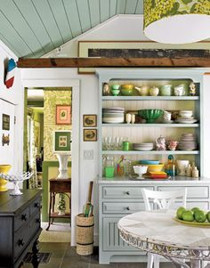 open shelving. colorful dishes. white walls. painted ceiling.