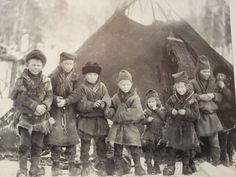 Nomadskolebarn framför skolkåta 1913 i Gällivare. Barnen har Gällivaredräkten som den såg ut då. Några bär de traditionella gällivaresamiska klädesmössorna matjuk för kvinnor/flickor och gáhper (mansmössa). Peskarna, vierggimuoddá, renskinnspälsarna har getskinnsbräm längst ner. Saami school children, 1913 Gällivare The children wear lulesaami clothing with the charateristics of the Gällivare-area including the hats, reindeer furs with hems decorated with goatfur. Photo taken by Oscar…