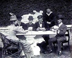 Young Tsarevich Nicholas Alexandrovich playing cards with cousins , Grand Duke George in the background .