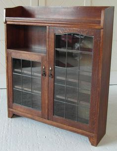 LX_44 Liberty & Co. Arts & Crafts 2 door bookcase in oak with leaded glazed doors and copper handles.  Liberty & Co. Circa 1900.