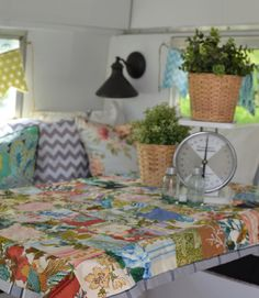 "Inside and out, The Crafty Camper showcases the DIY lifestyle. ""I wanted to keep it clever and economical,"" Denise says. Bunting with oil-cloth flags serve as valances without taking up space in the miniature vehicle, while oil-cloth pillows from fellow DIY expert Modern June create a cozy seating nook around the table. For craft workshops, Denise can fit about four women around the table inside the camper. She also sets up a large table outside to accommodate as many as 15 crafters. In this…"