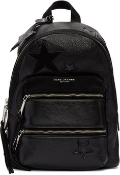 "Marc Jacobs: Black Star Patchwork Backpack |  Grained leather backpack in black. Tonal suede trim throughout. Star appliqués featuring alternating textures throughout. Carry handle. Star-shaped logo-embossed leather charm on detachable lanyard at handle base. Adjustable padded shoulder straps. Logo stamp in silver-tone and zippered compartments at face. Two-way zip closure at main compartment. Zip pocket at interior. Tonal textile lining. Silver-tone hardware. Tonal stitching. Approx.10""…"