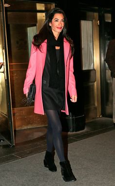 Classy Night Out from Amal Clooney's Best Looks  Flashing a grin, Amal makes her way out of a NYC hotel wearing a bubblegum pink coat over an all-black ensemble.