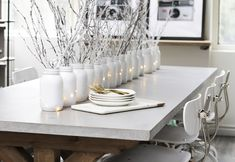 "Gorgeous AND affordable! Check out my top tips to creating this elegant winter white table #lilyshop #christmas #diy #howto #tablescape   I'm on a white kick lately. I want everything super clean and crisp so I thought it would be fun to decorate our table with an all white centerpiece. I'm in LOVE! Don't you feel like it's kind of snowing in our office?   Chick and Cheap: Spray-painted Mason Jars, twinkle lights and ""snow"" covered branches create an upscale rustic look.   Gold flatwar…"