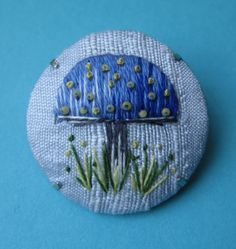 1 o 3 A beautifully hand embroidered blue toadstool in shades of blue. Worked in long and short stitch with tiny vintage green glass beads and french knots. Little blades of grass in green stitches and french knots add a little detail. The background fabric is a very pale blue silk. This is a fun little brooch that looks great on a denim jacket or a blazer. makes a lovely gift for a little girl too. 3 cms dia. Materials: silk, cotton, silver color brooch, thread, floss, beads. US$31.31