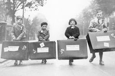 Child migrants arriving australia in 1938, carry their suitcases down the street,part of a exhibition that ran in sydney in 2010