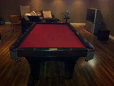 Brunswick dark cherry pool table updated with a red pool cloth.