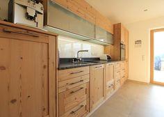 Moderne Holzküche: Küche in Fichte Altholz - mit schwarzer Steinarbeitsplatte mit naturgebrochener Kante. Planung und Umsetzung: Tischlerei Laserer