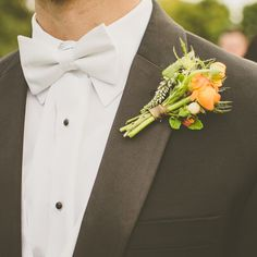 Groomsmen wowed with green boutonnieres accented with a pop of orange.